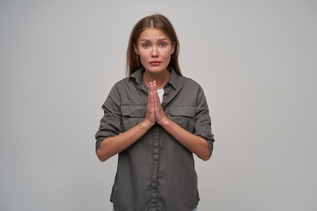 Tienermeisje, ongelukkige vrouw met bruin lang haar. het dragen van een grijs shirt en haar handpalmen bij elkaar houden, vraagt om iets. kijken naar de camera geïsoleerd over grijze achtergrond