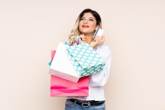 Tienermeisje op beige muurholding het winkelen zakken en een creditcard