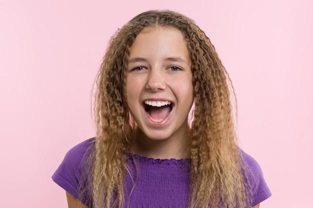 Tienermeisje op een roze achtergrond. gezichtsuitdrukkingen
