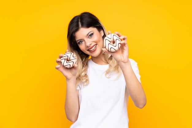 Tienermeisje op gele muurholding donuts met gelukkige uitdrukking