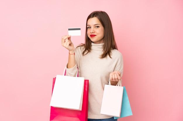Tienermeisje op roze het winkelen van de muurholding zakken en een creditcard wordt geïsoleerd die
