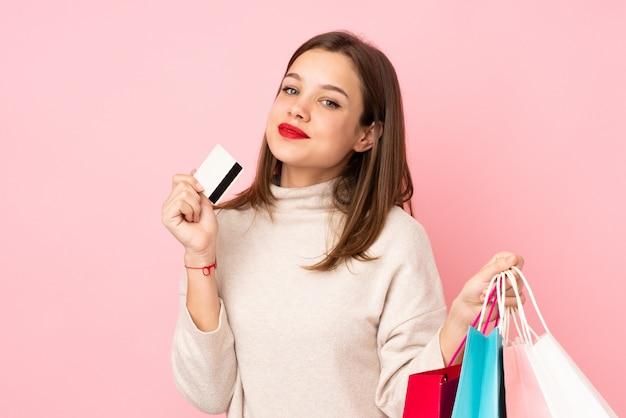 Tienermeisje op roze muurholding het winkelen zakken en een creditcard