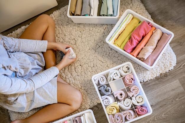 Tienermeisje opgerolde kleding gebruikt de marie kondos-methode om kleding in de kast te plaatsen