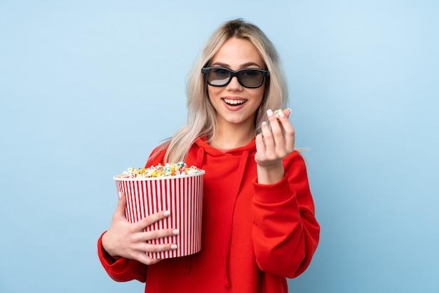 Tienermeisje over blauwe muur met 3d glazen en holding een grote emmer popcorns