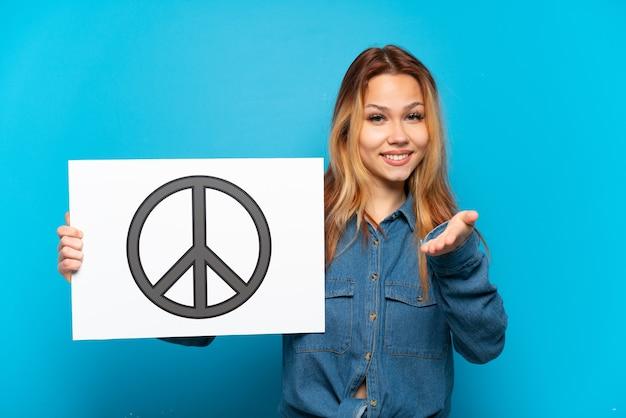 Tienermeisje over geïsoleerde blauwe achtergrond die een aanplakbiljet met vredessymbool houden dat een overeenkomst sluit