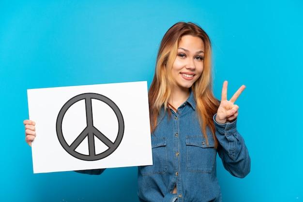 Tienermeisje over geïsoleerde blauwe achtergrond die een aanplakbiljet met vredessymbool houden en een overwinning vieren