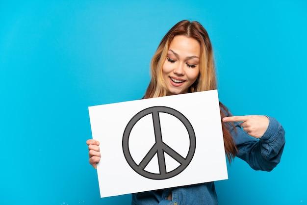 Tienermeisje over geïsoleerde blauwe achtergrond die een aanplakbiljet met vredessymbool houden en het richten