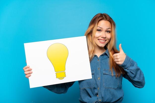 Tienermeisje over geïsoleerde blauwe achtergrond die een plakkaat met bolpictogram met omhoog duim houdt