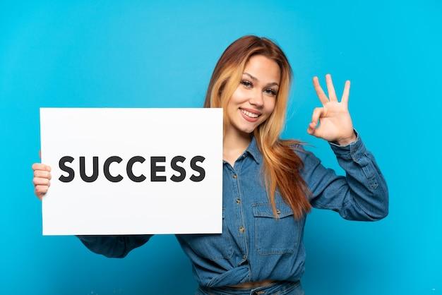 Tienermeisje over geïsoleerde blauwe achtergrond die een plakkaat met tekst succes houdt en een overwinning viert