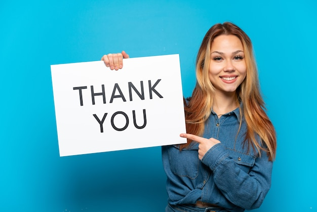 Tienermeisje over geïsoleerde blauwe achtergrond met een bordje met de tekst dank u en erop wijzend