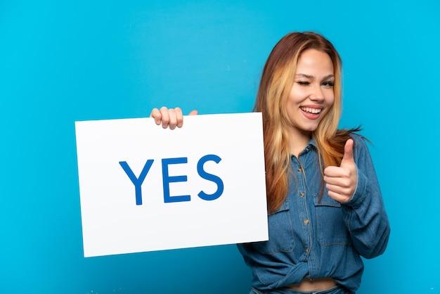Tienermeisje over geïsoleerde blauwe achtergrond met een bordje met de tekst ja en naar voren wijzend