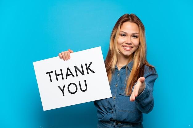 Tienermeisje over geïsoleerde blauwe achtergrond met een plakkaat met tekst bedankt om een deal te sluiten