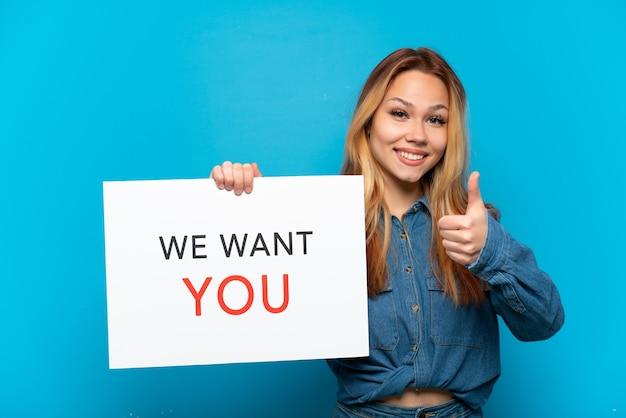 Tienermeisje over geïsoleerde blauwe achtergrond met we want you-bord met duim omhoog