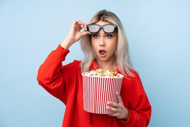 Tienermeisje over geïsoleerde blauwe muur die met 3d glazen wordt verrast en een grote emmer popcorns houdt