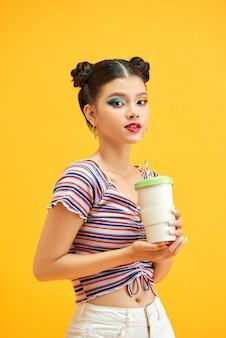 Tienermeisje over geïsoleerde gele achtergrond die een koffie houdt en drinkt om mee te nemen