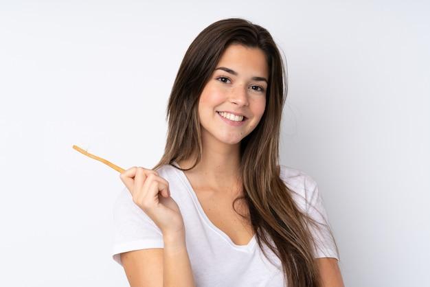 Tienermeisje over geïsoleerde muur met een tandenborstel