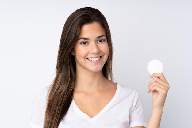 Tienermeisje over geïsoleerde muur met katoenen stootkussen voor het verwijderen van make-up uit haar gezicht en het glimlachen