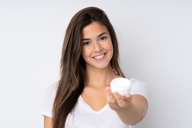Tienermeisje over geïsoleerde muur met vochtinbrengende crème en het aanbieden ervan