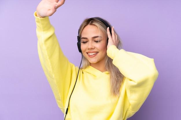 Tienermeisje over geïsoleerde purpere muur het luisteren muziek en het dansen