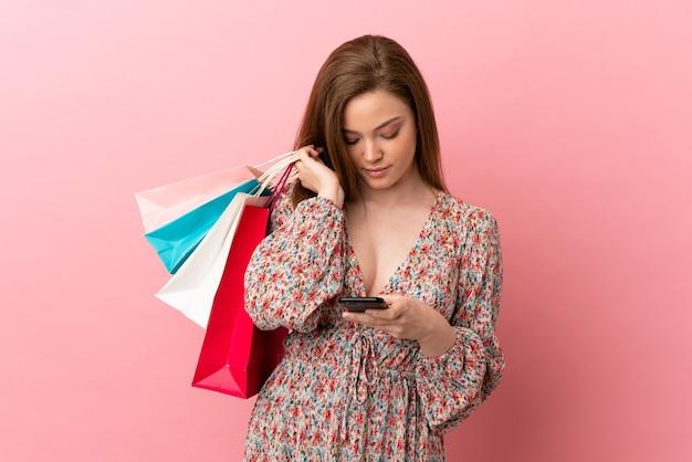 Tienermeisje over geïsoleerde roze achtergrond die boodschappentassen vasthoudt en een bericht schrijft met haar mobiele telefoon aan een vriend