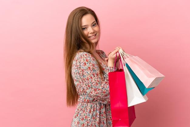 Tienermeisje over geïsoleerde roze achtergrond die boodschappentassen vasthoudt en glimlacht