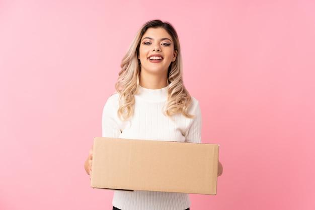 Tienermeisje over geïsoleerde roze achtergrond die een doos houden om het naar een andere plaats te verplaatsen