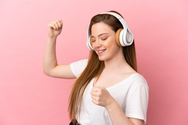 Tienermeisje over geïsoleerde roze achtergrond die muziek luistert en danst