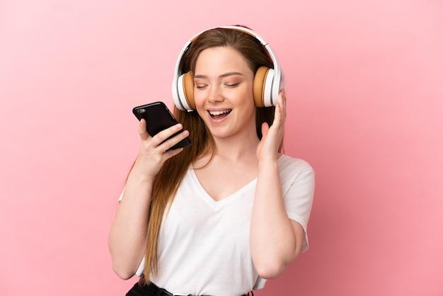 Tienermeisje over geïsoleerde roze achtergrond die muziek luistert met een mobiel en zingt