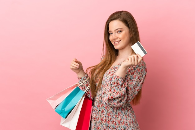 Tienermeisje over geïsoleerde roze achtergrond met boodschappentassen en een creditcard