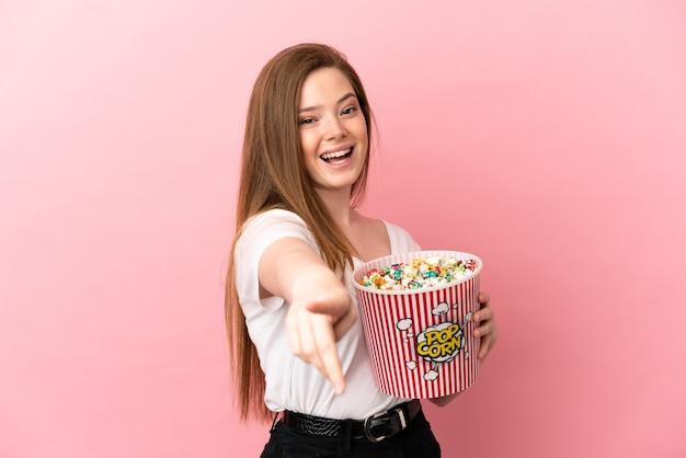 Tienermeisje over geïsoleerde roze achtergrond met een grote emmer popcorns terwijl ze naar voren wijst