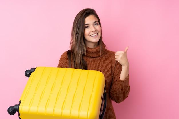 Tienermeisje over geïsoleerde roze muur in vakantie met reiskoffer en met omhoog duim