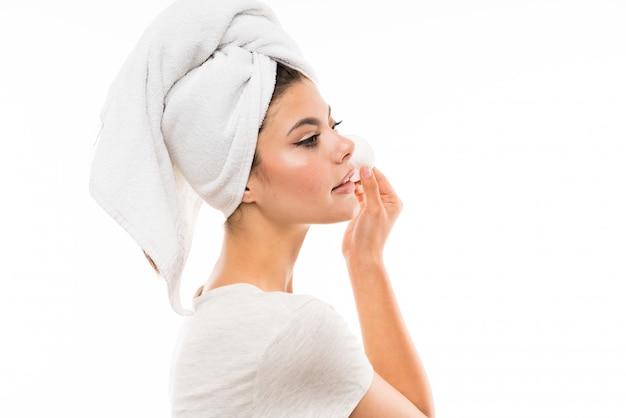 Tienermeisje over geïsoleerde witte wallremoving make-up van haar gezicht met katoenen stootkussen