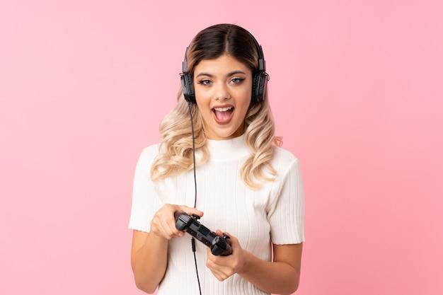 Tienermeisje over het geïsoleerde roze spelen bij videospelletjes