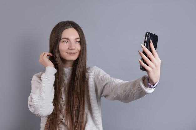 Tienermeisje selfie te nemen tijdens huiswerkvoorbereiding voor sociaal netwerk blog, kus tonen, plezier maken met camera, poseren voor foto, afgeleid van schooltaken, gadgetverslaving