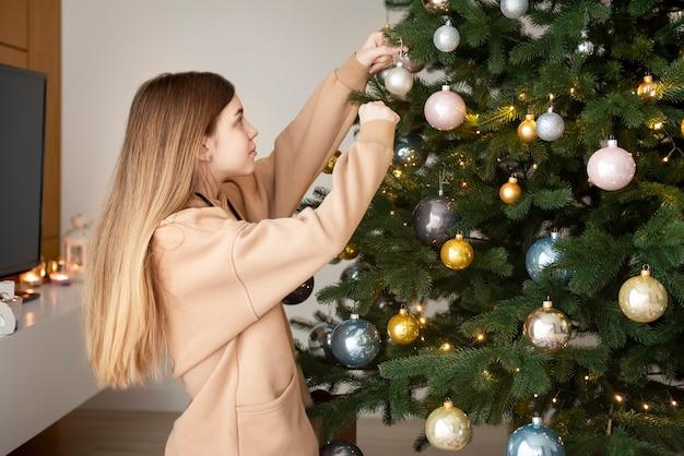 Tienermeisje siert de kerstboom. kerstboom in de woonkamer.
