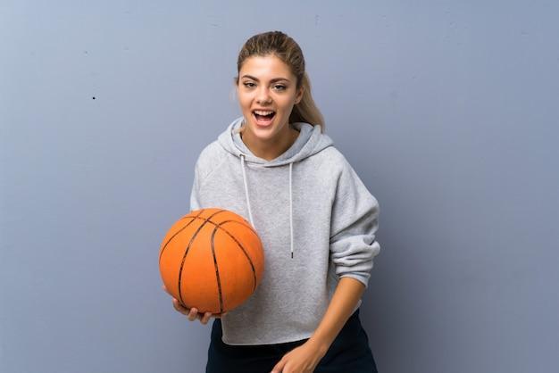 Tienermeisje speelbasketbal over grijze muur