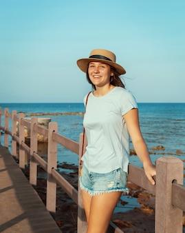 Tienermeisje staande op houten loopbrug aan zee bij zonsondergang, gekleed in lichtblauw t-shirt, strohoed en portemonnee. zomer reisconcept