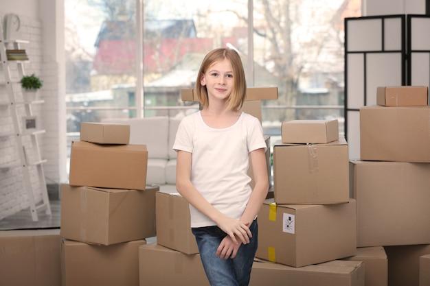 Tienermeisje staat in de buurt van kartonnen dozen in nieuw huis