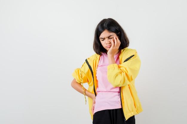 Tienermeisje staat in denkende pose in t-shirt, jas en kijkt verbaasd. vooraanzicht.