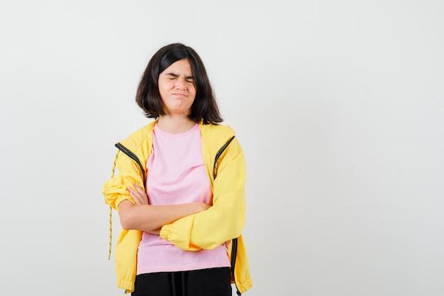Tienermeisje staat met gekruiste armen in geel trainingspak, t-shirt en kijkt boos, vooraanzicht.