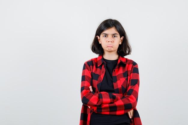 Tienermeisje staat met gekruiste armen in t-shirt, geruit hemd en kijkt boos, vooraanzicht.