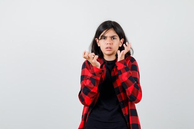 Tienermeisje steekt handen op in de buurt van gezicht in t-shirt, geruit hemd en kijkt perplex. vooraanzicht.