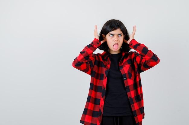 Tienermeisje stopt oren met vingers, steekt tong uit in casual shirt en ziet er speels uit, vooraanzicht.