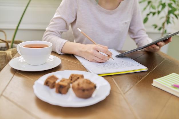 Tienermeisje studeert thuis, jonge student zit aan tafel met behulp van digitale tablet, schoolnotitieboekjes, schoolboeken. online leren op afstand, technologie, onderwijsconcept