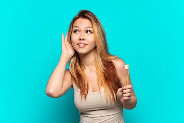 Tienermeisje tandenpoetsen over geïsoleerde blauwe achtergrond die aan iets luistert door hand op het oor te leggen