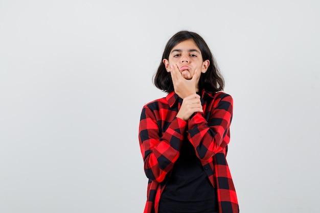 Tienermeisje trekt haar huid naar beneden in t-shirt, geruit hemd en ziet er teleurgesteld uit. vooraanzicht.