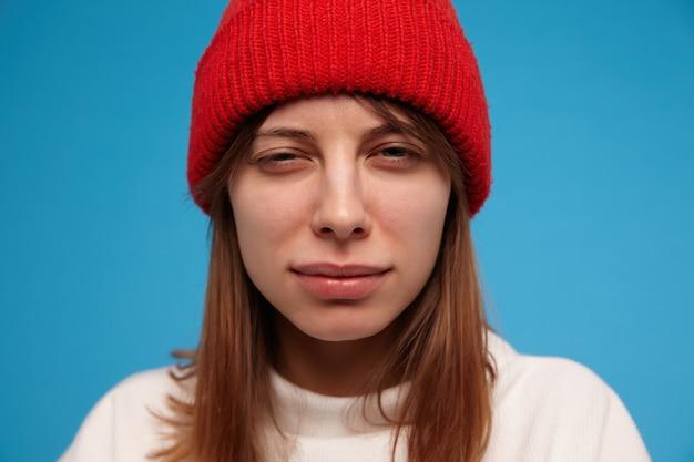 Tienermeisje, verdacht uitziende vrouw met donkerbruin haar. het dragen van een witte trui en een rode hoed. mensen en emotioneel concept. close-up, geïsoleerd over blauwe muur