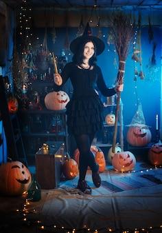 Tienermeisje verkleed als heks met pompoenen op de achtergrond van decor voor halloween