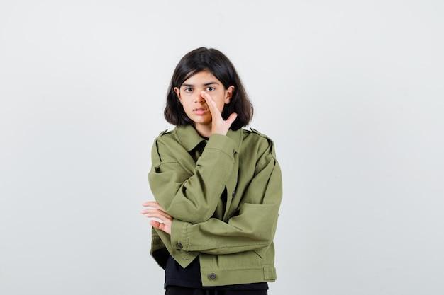 Tienermeisje vertelt geheim achter hand in t-shirt, groene jas en kijkt voorzichtig, vooraanzicht.