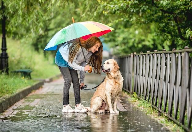 Tienermeisje wandelen met golden retriever hond op regenachtige dag
